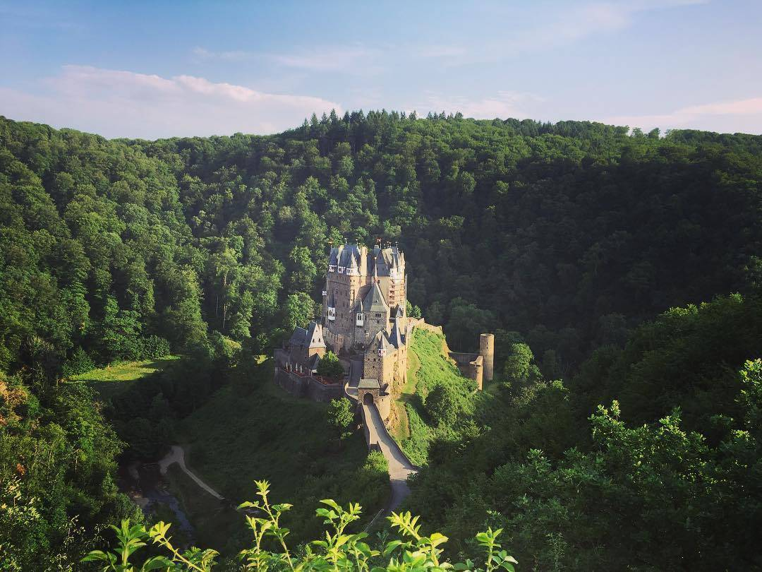 Wide shot of Eltz Castle in Germany and the surrounding forest